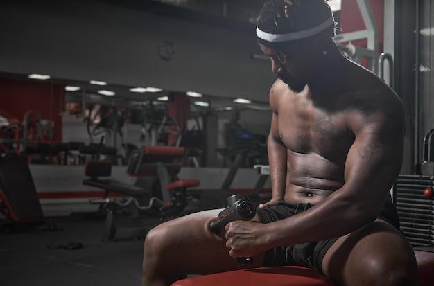 Un masseur à percussion fait du sport avec un afro-américain massant la hanche pour soulager les muscles assis sur le poids