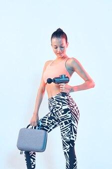 Masseur à percussion, jeune femme athlétique fit montrant un pistolet de massage portable en néon studio light