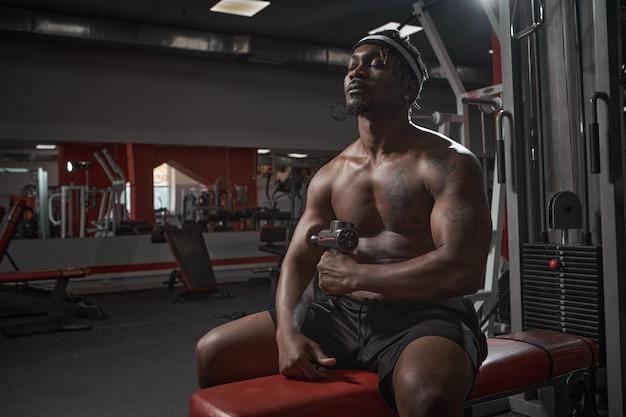 Masseur à percussion mec afro-américain athlétique massant la récupération après l'entraînement à la main dans la salle de sport