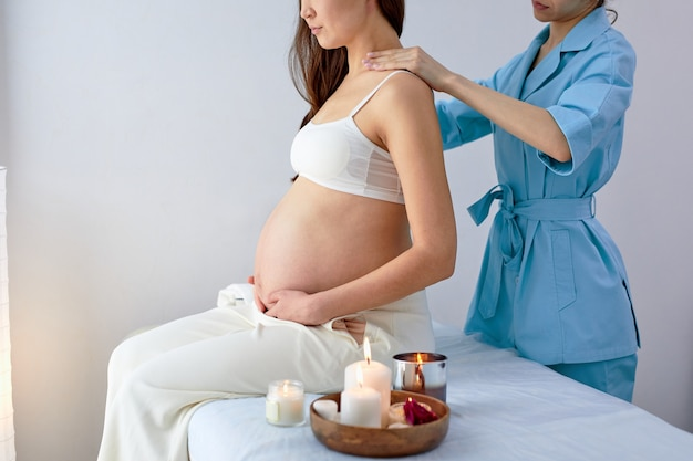Masseur physiothérapeute en uniforme bleu massant le dos d'une femme enceinte dans un centre de spa, vue latérale. la future maman se prépare à accoucher dans peu de temps. notion de grossesse. photo recadrée