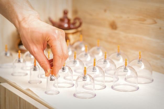 Masseur prend des bocaux en verre de massage sous vide de la thérapie traditionnelle chinoise par ventouses de la table dans le spa
