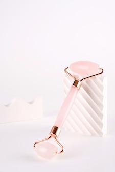 Masseur à rouleaux de visage rose fabriqué à partir de pierre de quartz naturelle sur fond blanc. soin liftant et tonifiant à domicile.