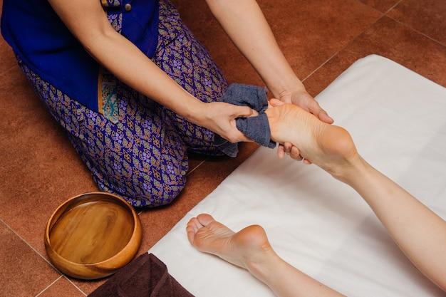 Un masseur thaïlandais en ostume asiatique fabrique des procédures de spa traditionnelles avec des jambes féminines.