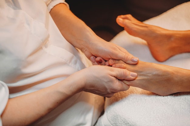 Masseur travaille avec les jambes du client lors d'une procédure de spa au salon