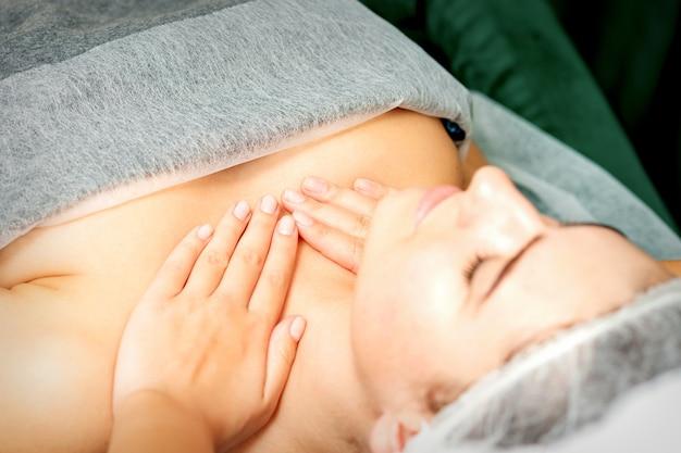La masseuse fait un massage de poitrine d'une jeune femme caucasienne dans un salon de station thermale