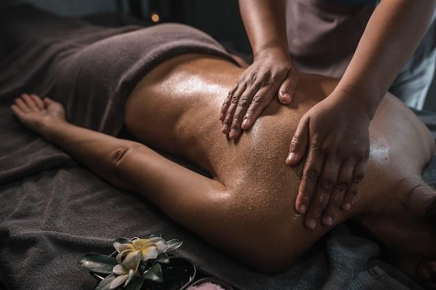 Masseuse massant le dos d'un jeune homme avec de l'huile et du sucre