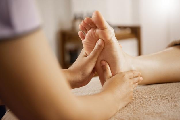 Masseuse massant le pied féminin au spa.