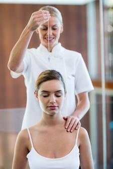 Masseuse tenant un pendentif sur la tête de la femme