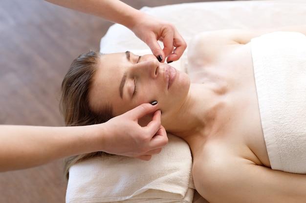 Massez le visage d'une femme sur le canapé. masseur dans le salon