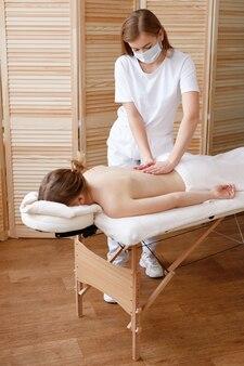 Massothérapeute dans un masque fait un massage en quarantaine