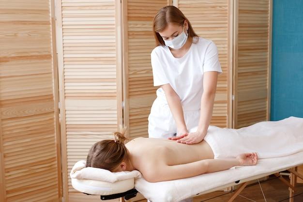 Massothérapeute dans un masque fait un massage