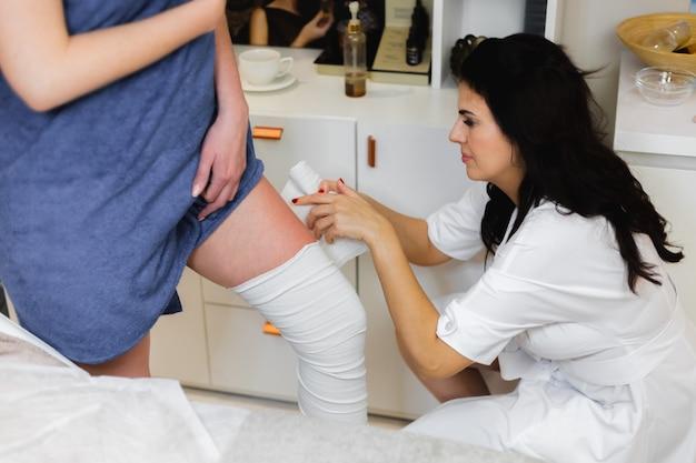 Le massothérapeute dans le salon de beauté du spa fait un enveloppement au client pour remettre le corps en forme, se débarrasser des poches