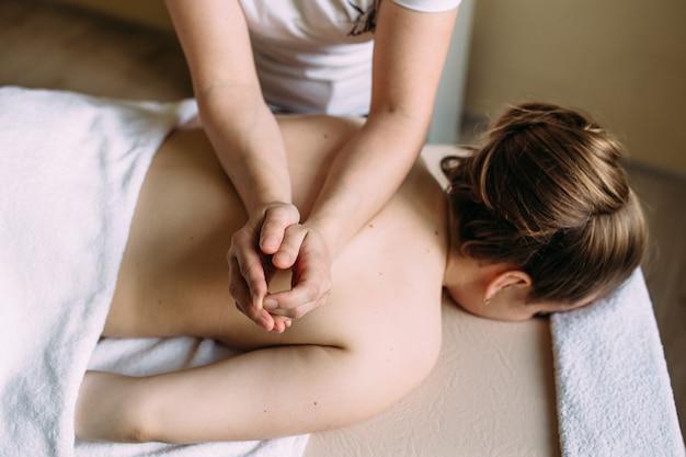 Massothérapeute faisant un massage sur le corps féminin dans le spa