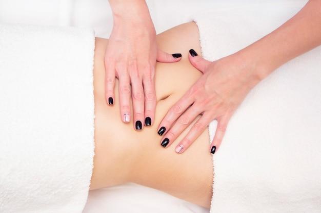 Massothérapeute massant l'estomac d'une femme. massage et soins corporels. spa corps massage femme mains traitement.
