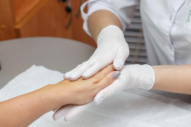 Massothérapeute massant les mains d'une femme dans un salon de beauté