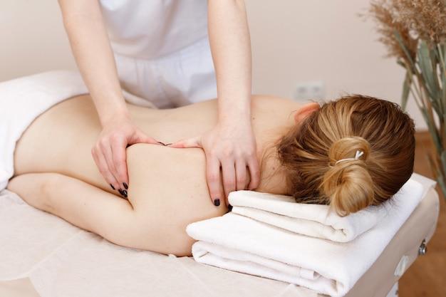 Le massothérapeute masse le dos de la fille. salon de thalassothérapie