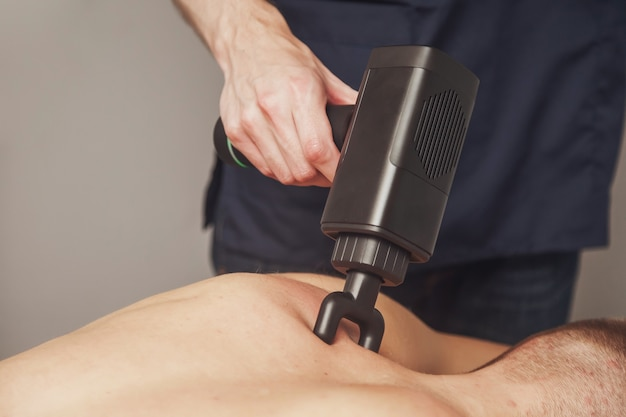 Le massothérapeute traite les blessures du patient masculin athlète professionnel. massages de choc au pistolet sportif dans le cabinet médical de la salle de sport. thérapie par percussion pour le massage de régénération du corps athlétique. physiothérapie