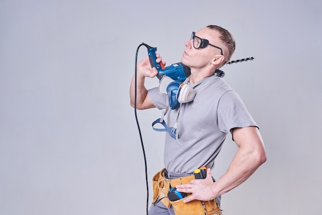 Master builderfinisseur en tenue de travail avec un perforateur sur l'épaule