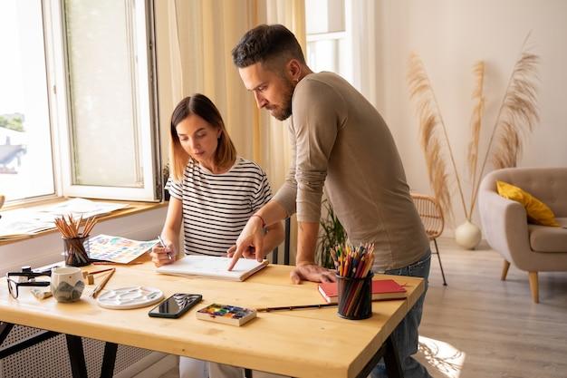Master class en école d'art. la jeune fille dessine un portrait à la peinture à l'huile et le professeur commente le travail en cours d'exécution. cours de dessin pour adultes.