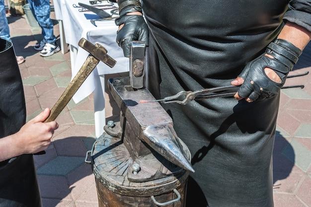 Master class en forge le forgeron apprend au garçon à fabriquer un souvenir en fer chaud