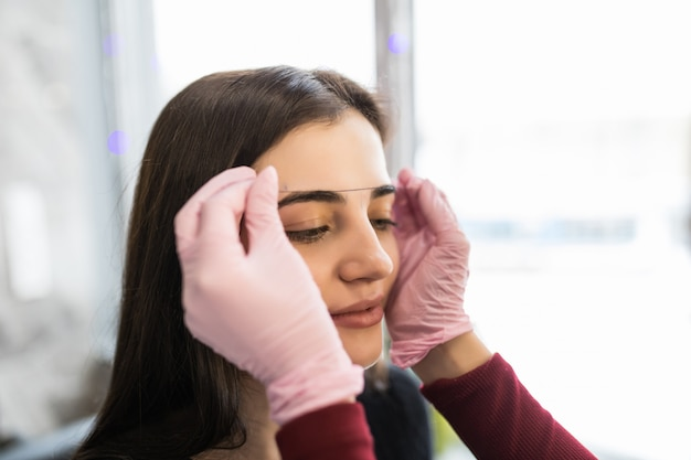 Master femelle en gants blancs vérifie le contour des sourcils avec du fil