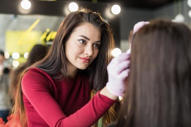 Master féminin faisant maquillage professionnel de jeune femme