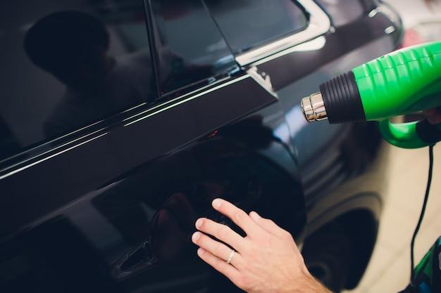 Master installe un film teinté pour voiture avec sèche-cheveux. voiture de protection de concept