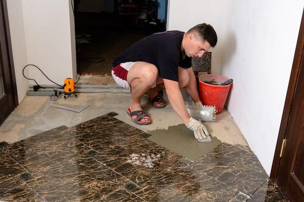 Master man pousse une spatule avec une solution de colle sur la surface de ciment pour la pose de carreaux de marbre