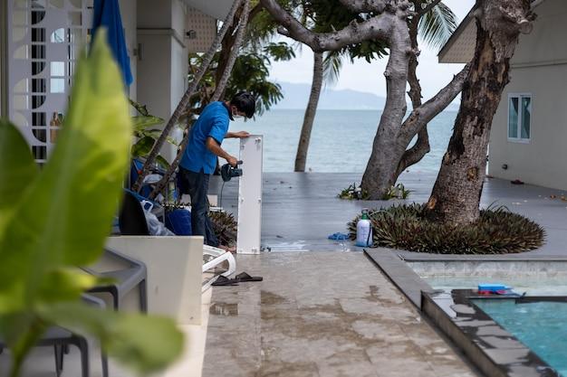 Master men nettoie le climatiseur dans un hôtel tropical.