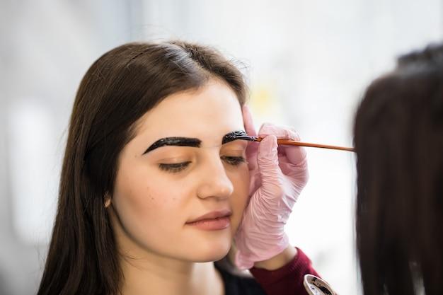 Master avec pinceau maquillant avec de larges lignes de sourcils noirs
