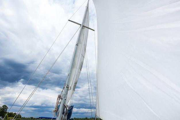 Mât de yacht avec une voile blanche le yacht se déplace avec une voile de voile blanche sur fond