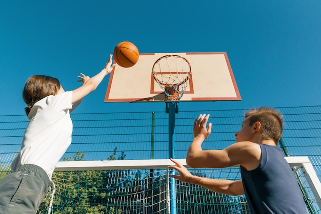 Match de basket-ball de streetball avec deux joueurs, adolescents fille et garçon