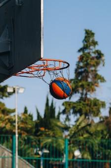 Match de basket de rue. bouclier de basket-ball, le ballon vole vers le panier. lancer précis dans l'anneau de basket-ball. concept de sport. match de basket de rue. basketball