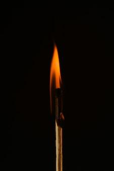 Match de gravure en gros plan sur un noir. flamme rouge. allumette d'allumage isolée sur fond noir. copiez l'espace.