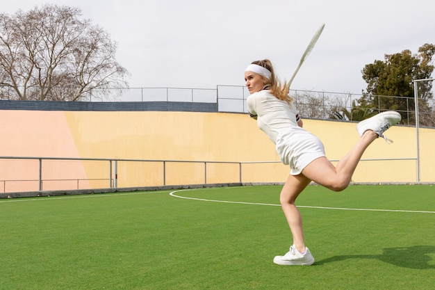 Match de tennis avec la jeune athlète en phase de frappe