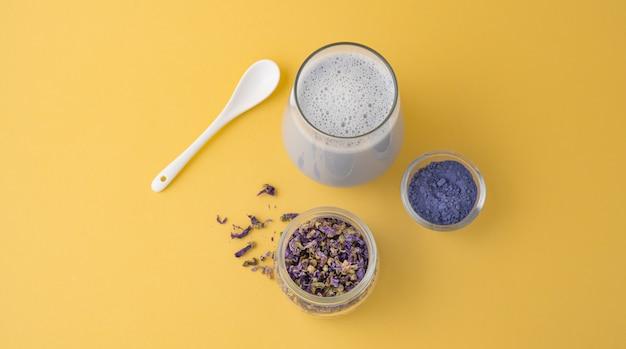 Matcha latte bleu et fleurs sur fond jaune