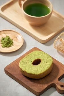 Matcha de thé vert dans une tasse en bois avec un gâteau allemand sur le gros plan de tapis marron