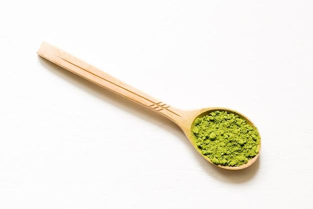 Matcha. thé vert en poudre japonais dans une cuillère sur un fond blanc.
