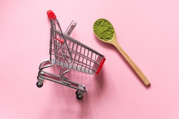 Matcha. thé vert en poudre japonais dans une cuillère sur un fond rose. chariot de caddie.