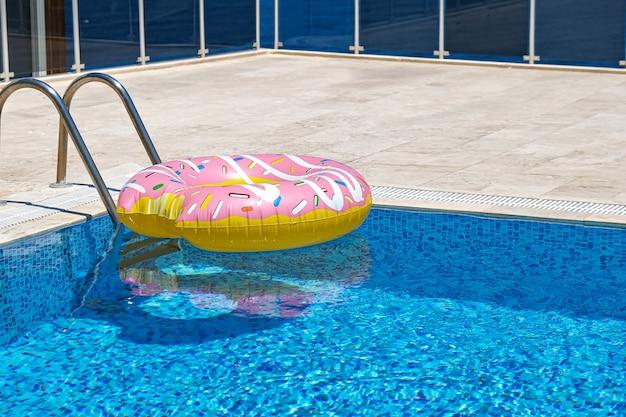 Matelas flottant en forme de beignet gonflable rose dans la piscine