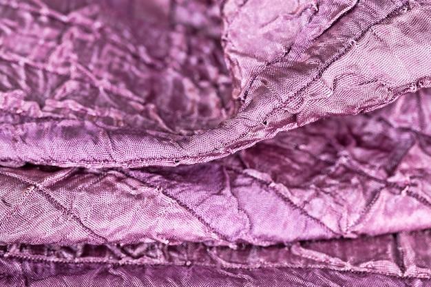 Un matériau artificiel de couleur pourpre avec une structure cousue irrégulièrement, des chiffons de gros plan, une couleur agréable