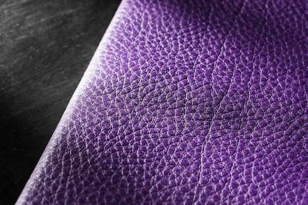 Matériau en cuir violet de qualité sur fond sombre