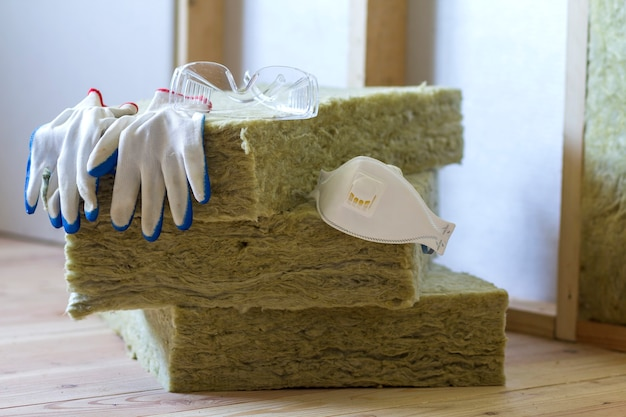 Matériau isolant en laine de roche et fibre de verre pour barrière contre le froid. outils pour travailler avec de la laine de verre: lunettes de protection, lunettes et masque. concept chaleureux de maison, économie, construction et rénovation.