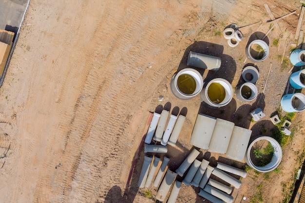 Matériaux de construction sur la pile de nouveaux tuyaux en béton des eaux usées d'égout de trou d'homme dans le chantier de construction