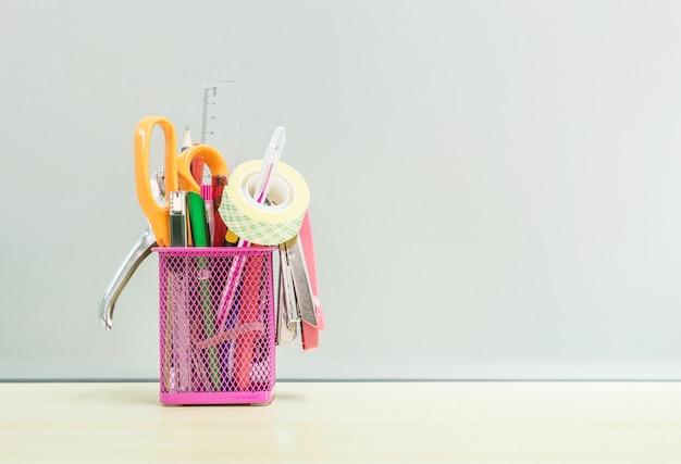 Matériel de bureau closeup avec boîte en acier rose sur un bureau en bois dans le bureau de travail