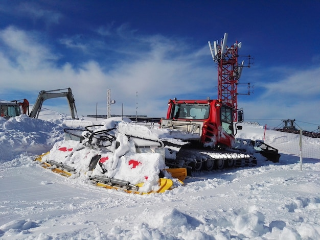 Matériel de déneigement couvert de neige sur la pente d'une station de ski d'hiver