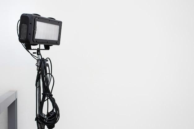Matériel léger de tournage avec de longs câbles avec mur blanc