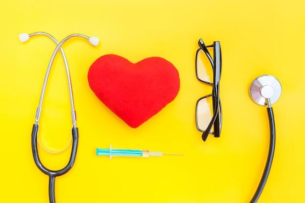 Matériel de médecine de conception tout simplement minimal stéthoscope ou phonendoscope lunettes seringue coeur rouge isolé sur jaune tendance
