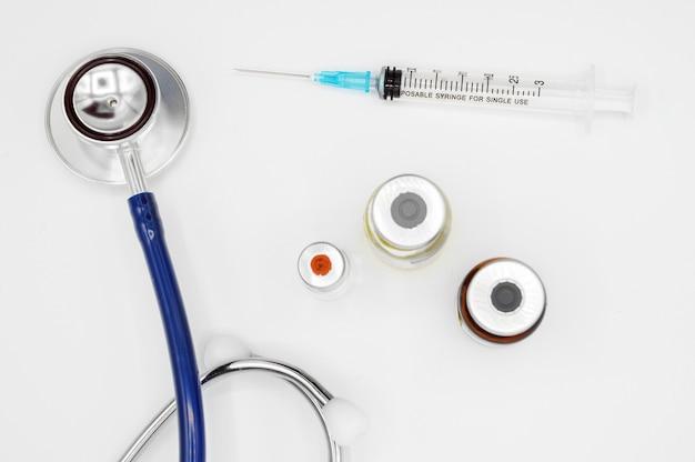 Matériel médical sur le bureau du médecin, ampoules de stéthoscope et seringue sur fond blanc avec espace de copie, gros plan. concept de soins de santé.