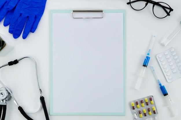 Matériel médical avec des pilules et du papier vierge sur le presse-papiers sur fond blanc